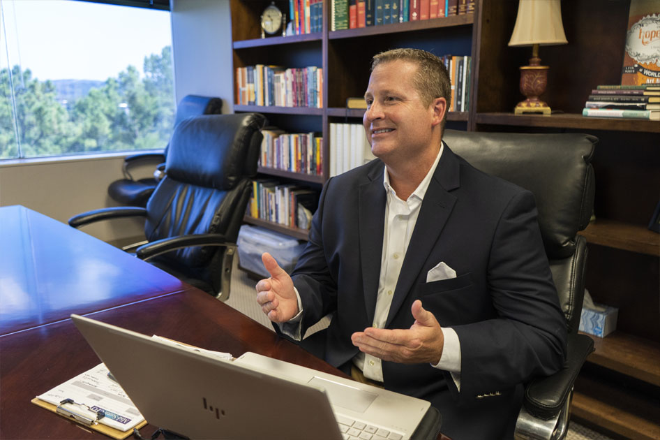 Jason talking to a client at his desk